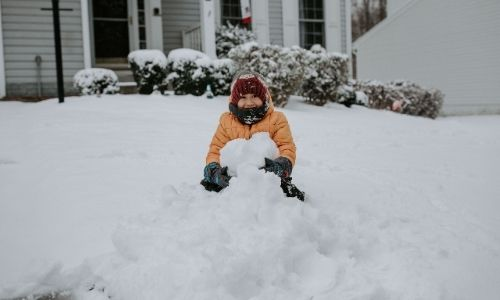 kid playing in snow pile